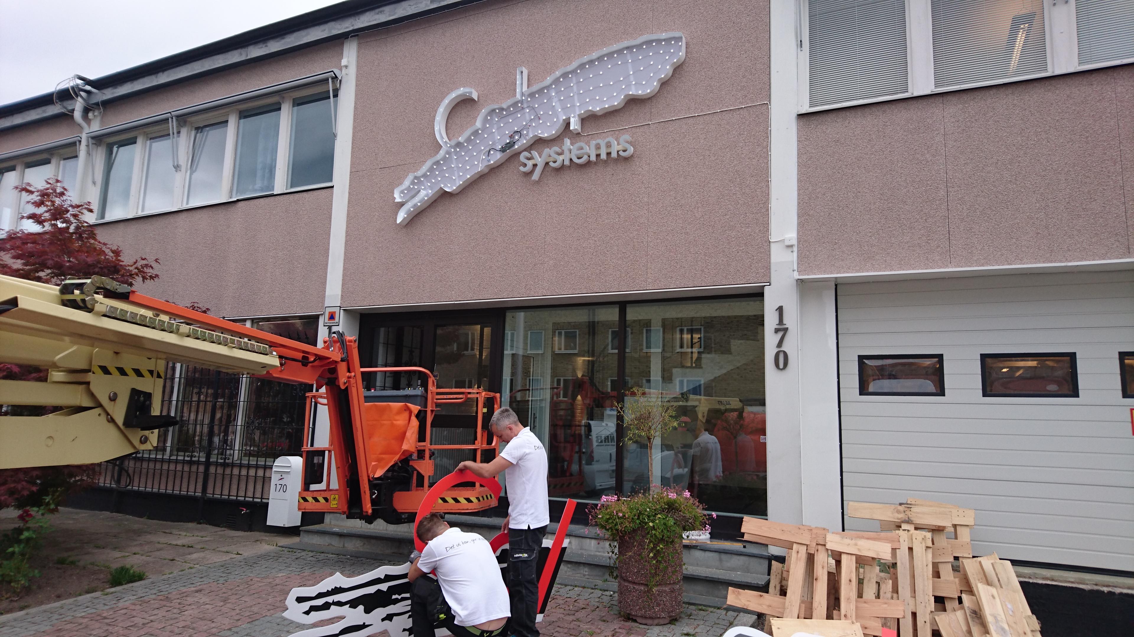 Hillstedts Skylt & Dekor sätter upp skylten utanför ColorSystems nya lokaler.