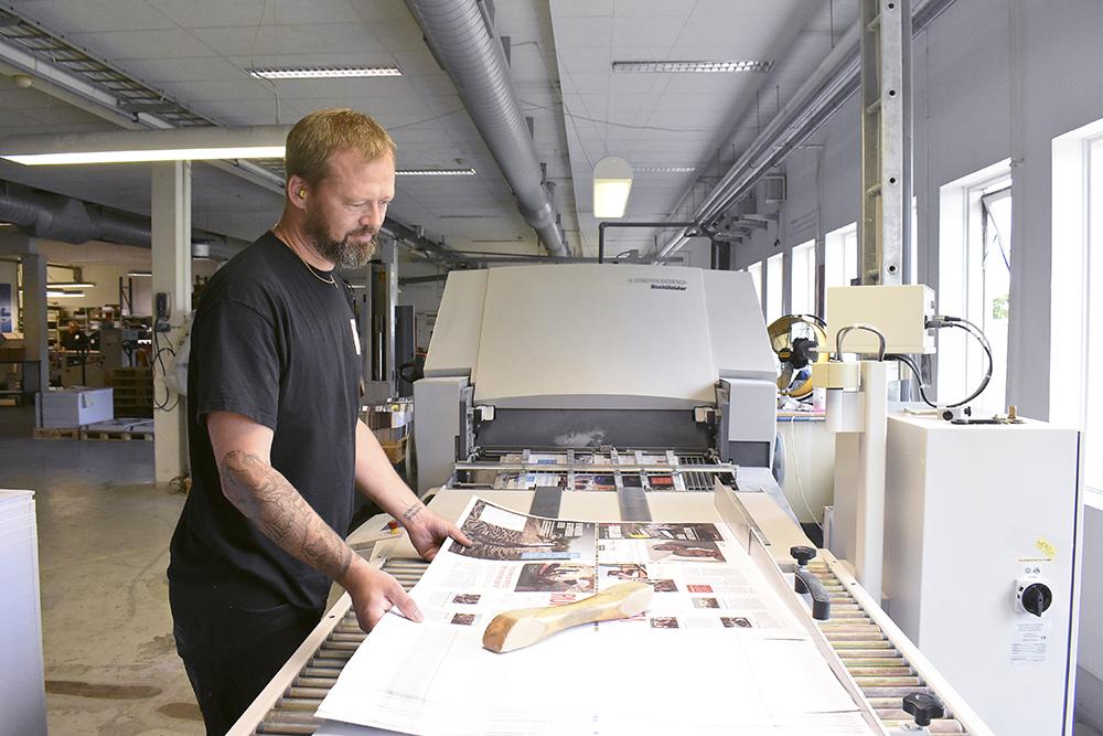 Jesper Dolleris snyggar till arkhögen innan den ska igenom falsmaskinen.