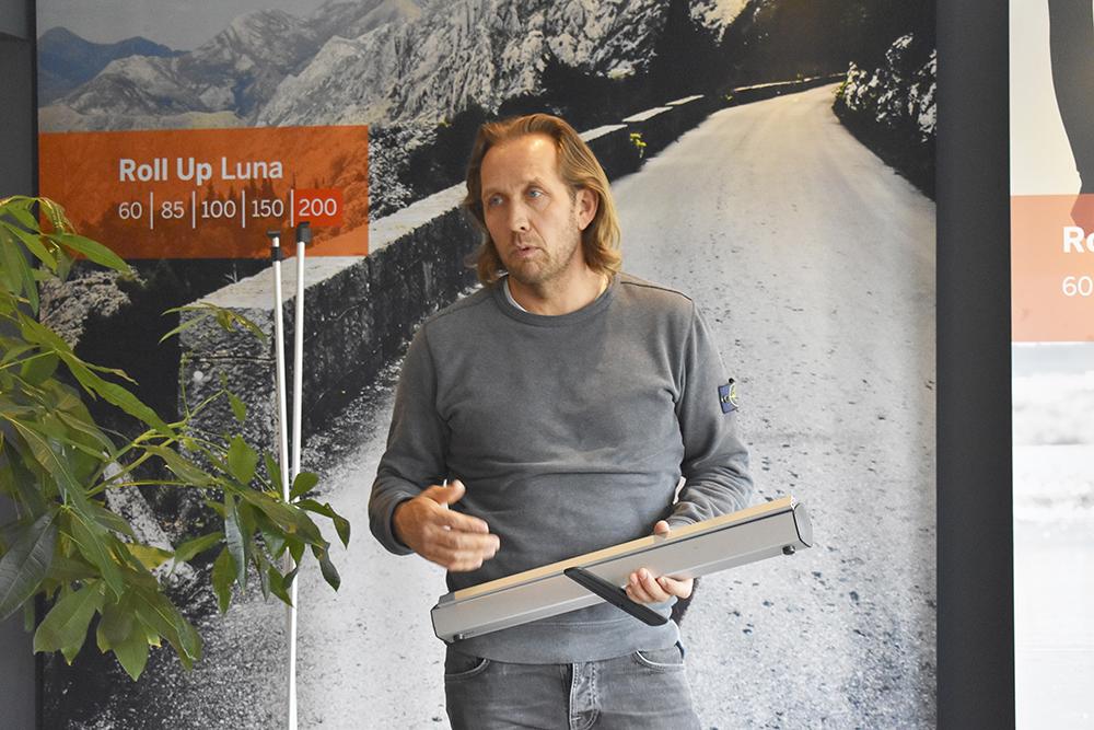 Johan Spennare med en egenutvecklad rollup. Genom att utrusta med teleskoppinne och extra lång fjäder, så kan även korta personer sätta upp höga rolluper. Och det är livstids garanti på dem.