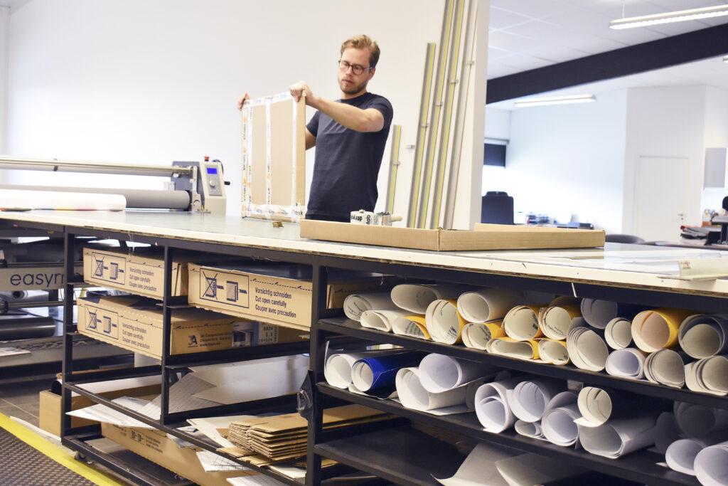 Skylt- och storformatsprodukter är ena stommen i verksamheten. Här ses Robin Elmgren arbeta vid paketeringsbordet.