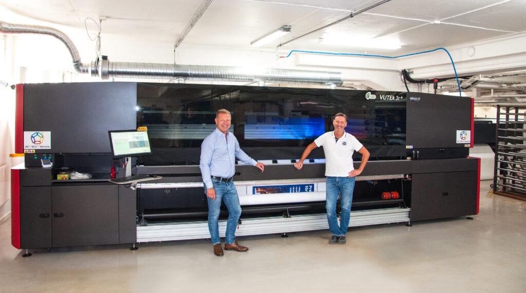 Till vänster Patrick Nermark, vd, och Peter Andersson, delägare och prepress operatör framför den nya rulle till rulle-printern.