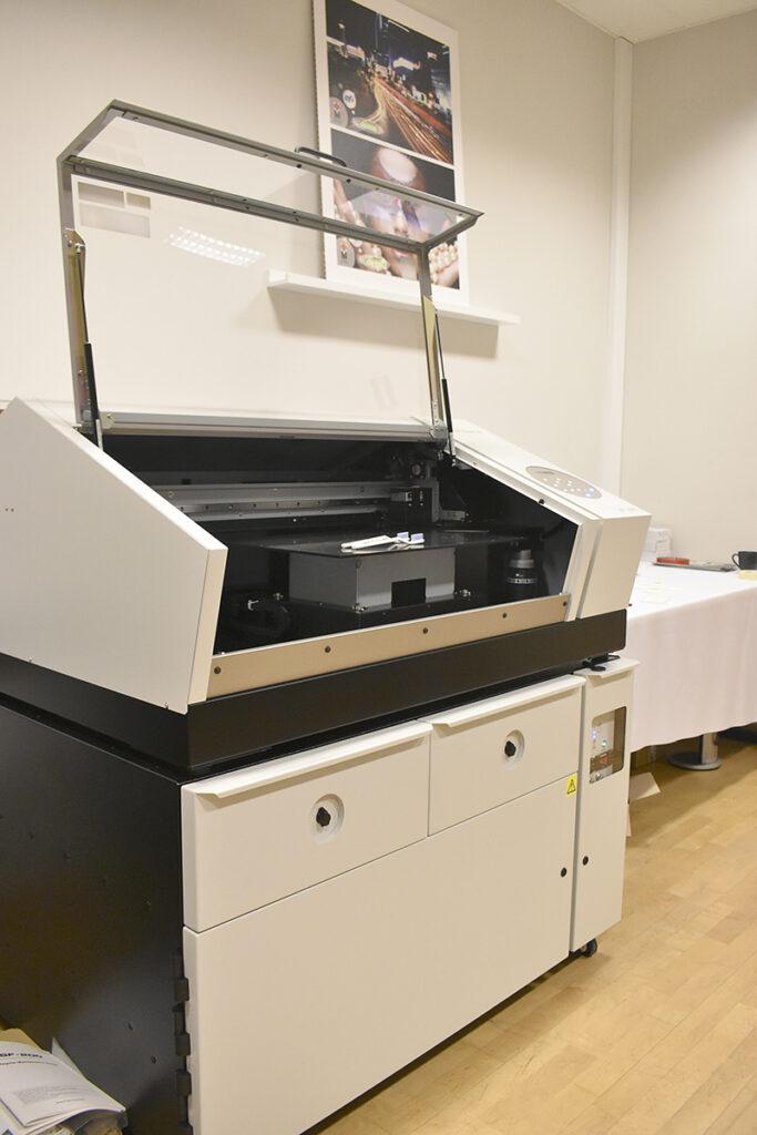 Maskinen har två fack. Ett värmeskåp för förvärmning av materialen innan utskrift, och ett torkskåp.