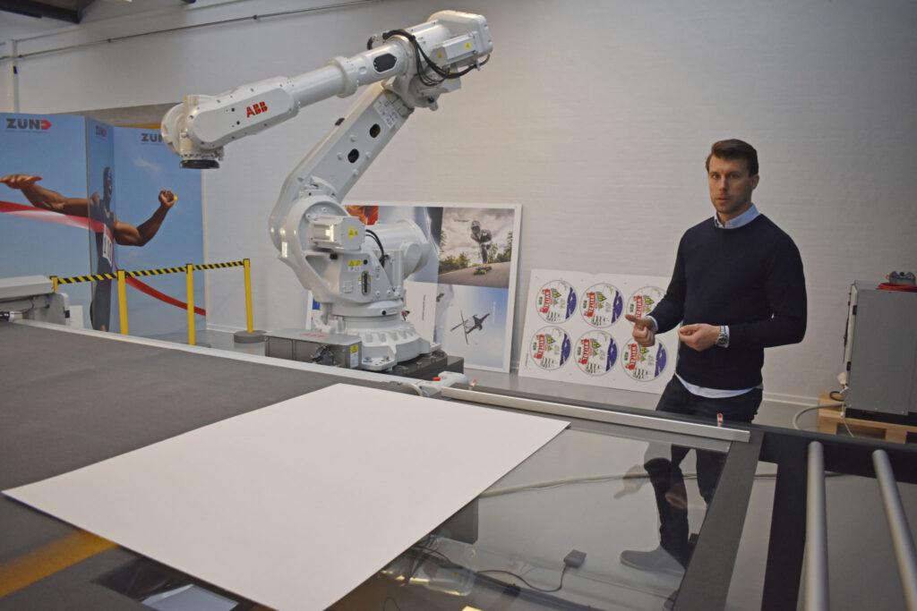 Martin Roed visar funktionen hos den nyutvecklade lösningen med ett glasbord och underliggande kamera. Det förenklar mycket när något ska skäras på baksidan.
