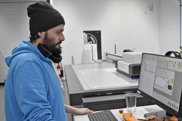 Mohammed Khalili står vid Swissqprints planprinter Nyala som används för att printa mycket aluminium och mässing.